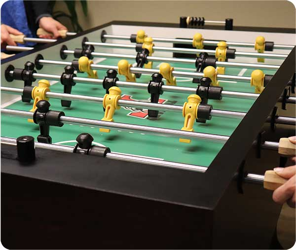 photo of employees playing fuseball as part of Insurance Technologies workplace benefits